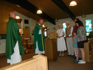 Fr. Andrew Duncan, Bishop Etienne, and Holiday family during Mass at St. Anthony, Guernsey, Wyoming.