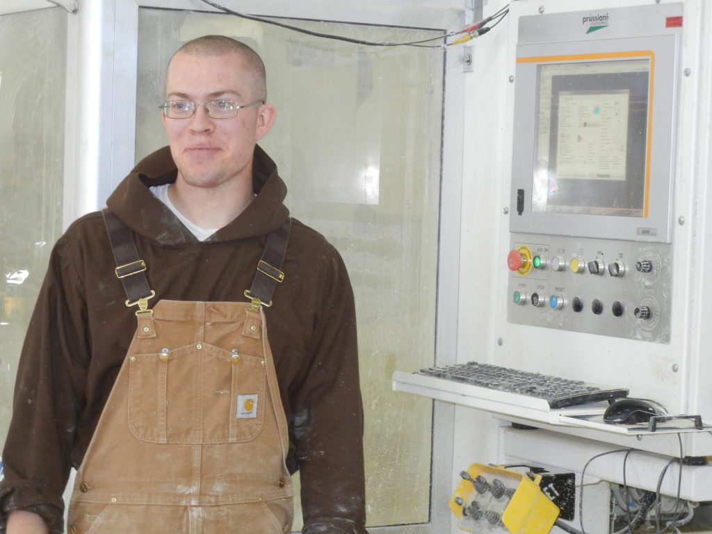 Br. Isidore Mary stands in front of the controls of the stone cutting equipment.  He is becoming quite the stone mason!