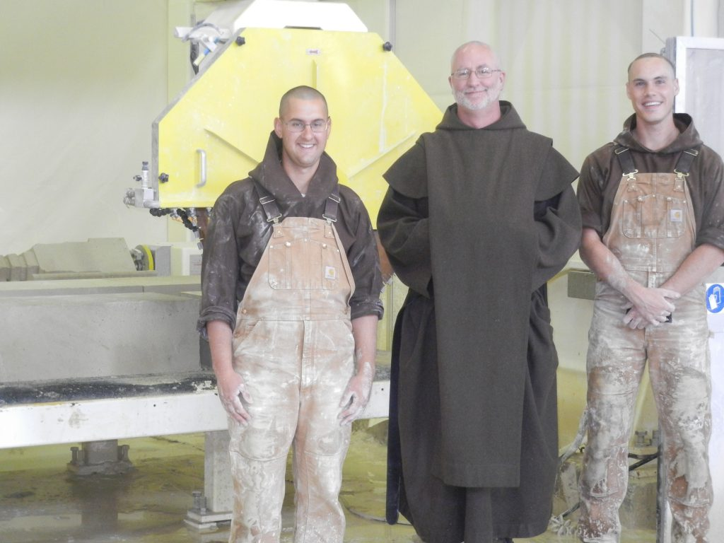 Br. Joachim Mary, Prior, Fr. Daniel Mary, and Br. John in front of the stone cutting machine.